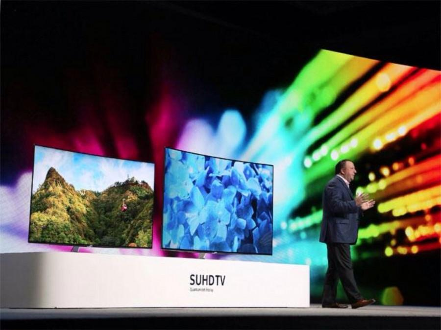 Samsung President and CEO of Samsung Electronics America shows off the SUHD TV Quantum Dot display television at CES on January 6, 2016.