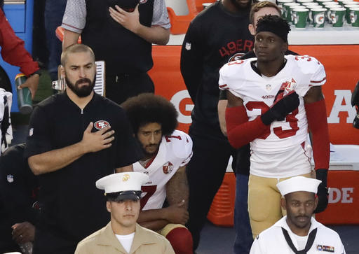 In this Thursday, Sept. 1, 2016 file photo, San Francisco 49ers quarterback Colin Kaepernick, middle, kneels during the national anthem before the team's NFL preseason football game against the San Diego Chargers, in San Diego. NFL Commissioner Roger Goodell disagrees with Kaepernick's choice to kneel during the national anthem, but recognizes the quarterback's right to protest.  (AP Photo/Chris Carlson, File)
