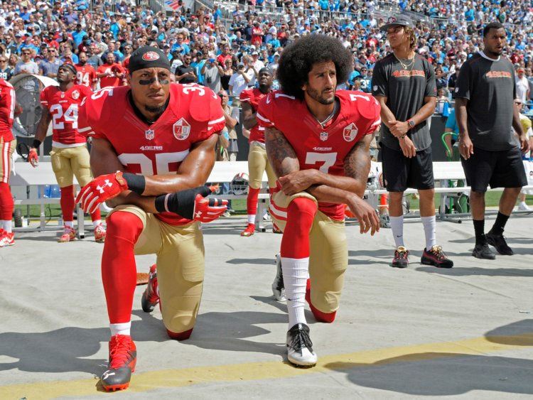 Former+49ers+players+Collin+Kaepernick+and+Eric+Reid+take+a+knee+during+the+national+anthem.