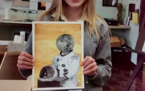 Senior Katie Ellsworth holding one of her art pieces about the moon landing.