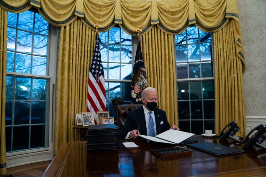 President Joe Biden signs a series of executive orders in the Oval Office of the White House, Wednesday, Jan. 20, 2021, in Washington. (AP Photo/Evan Vucci)